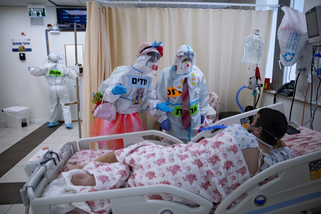 Clowns wearing protective equipment entertain a COVID-19 patient in the intensive care ward for coronavirus patients at Shaare Zedek Medical Center in...