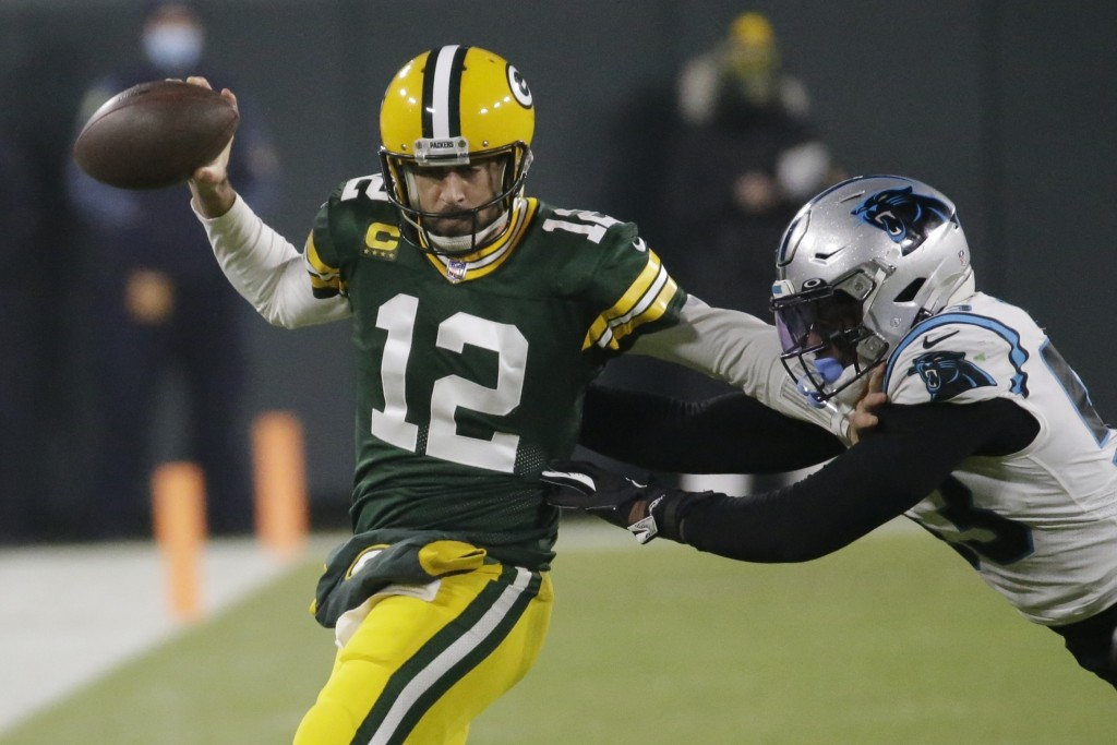 Green Bay Packers' Aaron Rodgers tries to run past Carolina Panthers' Brian Burns during the first half of an NFL football game Saturday, Dec. 19, 202...