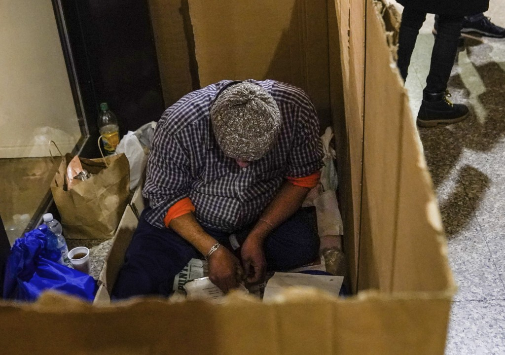 A homeless prepares to eat a free meal received from Progetto Arca Onlus inside a makeshift cardboard pallet in downtown Milan, northern Italy, Friday...