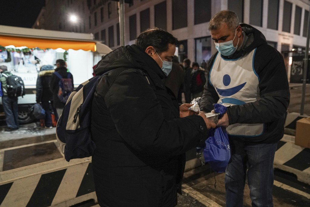 Maurizio Perrone, left, receives a free meal from volunteer Mouhib Abdelilah, at the Progetto Arca food truck in downtown Milan, northern Italy Thursd...