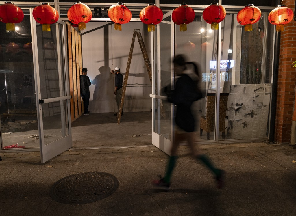 A runner jogs past a former Chinese restaurant being converted into an artist space in the Chinatown district of Los Angeles, Thursday, Dec. 17, 2020....