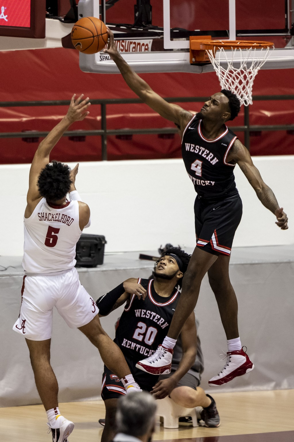 Western Kentucky guard Josh Anderson (4) blocks a shot from Alabama guard Jaden Shackelford (5) during the first half of an NCAA college basketball ga...