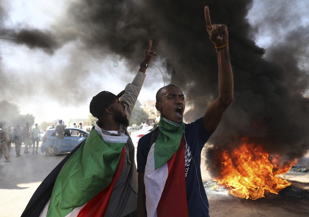 A demonstrator gives the victory sign during a protest, in Khartoum, Sudan, Saturday, Dec. 19, 2020.  Protests in Sudan's capital and across the count...