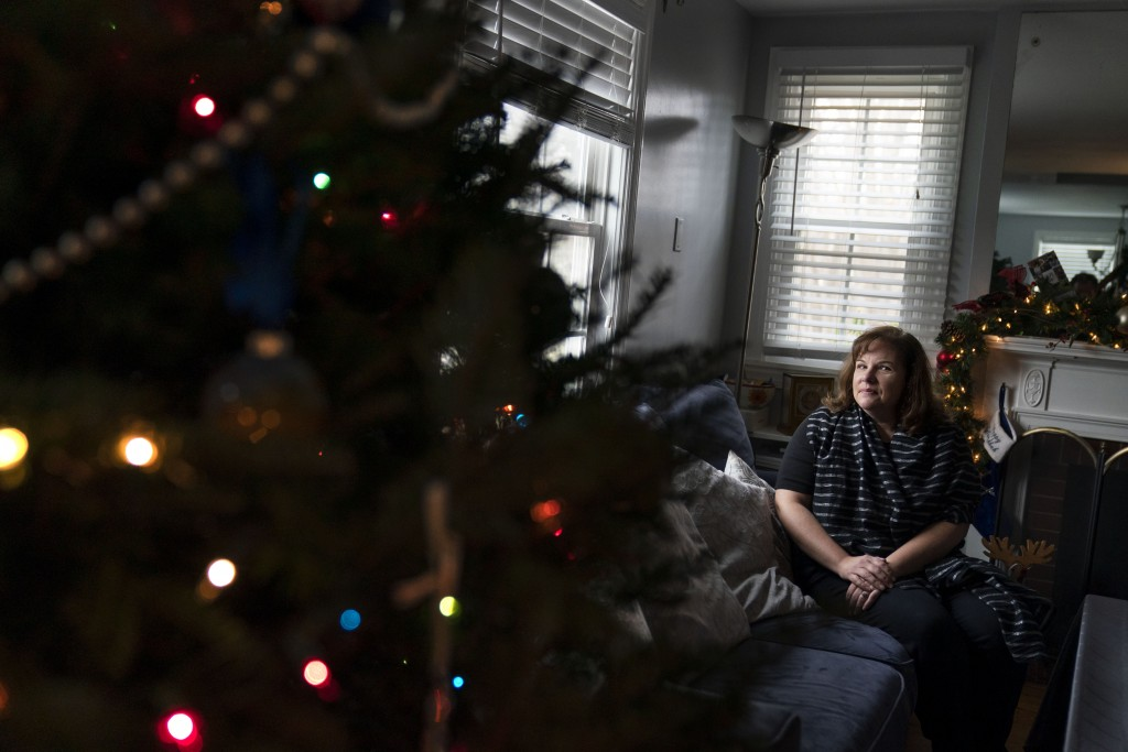 Eileen Carroll sits for a portrait in her home in Warwick, R.I, Wednesday, Dec. 16, 2020. When Carroll's daughter tested positive for the coronavirus,...