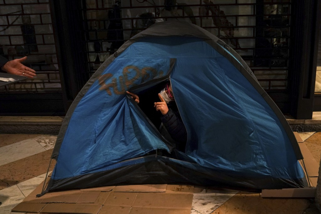 A homeless talks from inside his tent to a volunteer of the Progetto Arca Onlus during the distribution of free meals in downtown Milan, northern Ital...