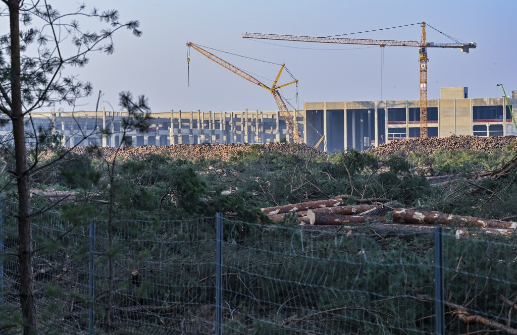 FILE - In this Dec. 8, 2020 file photo, felled trees lie on the construction site of the Tesla Gigafactory in Gruenheide near Berlin, Germany. A Germa...