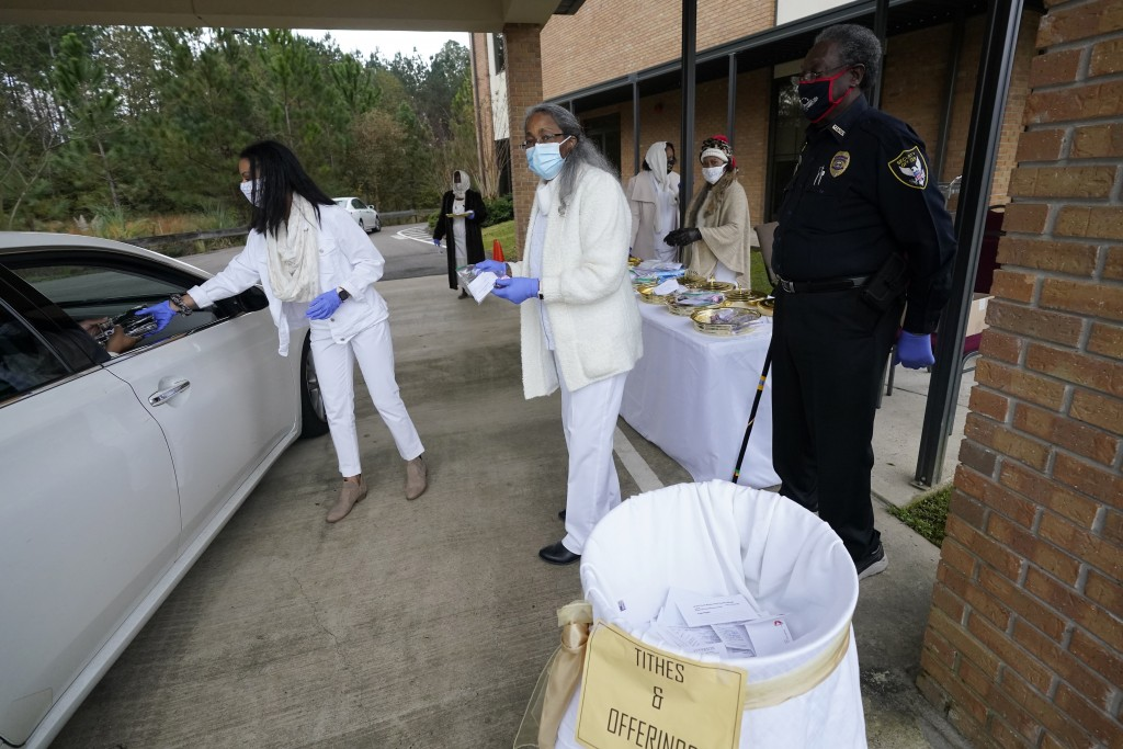 Ushers prepare collect offerings, distribute communion packets and distribute some personal protection products to members arriving for the First Sund...