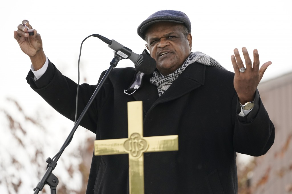 Anderson United Methodist Church senior pastor Rev. Joe May, holds part of the communion packet in his hand as he presides over an outdoor First Sunda...