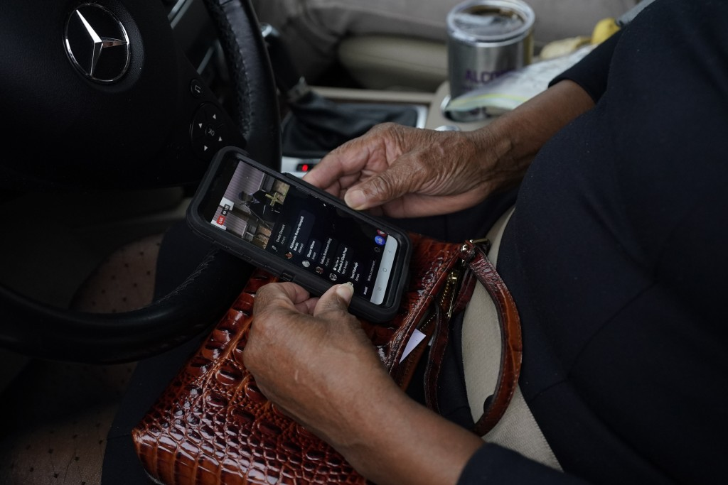 An Anderson United Methodist Church member monitors the First Sunday service live cast on her cellphone Dec. 6, 2020, in Jackson, Miss. The church has...