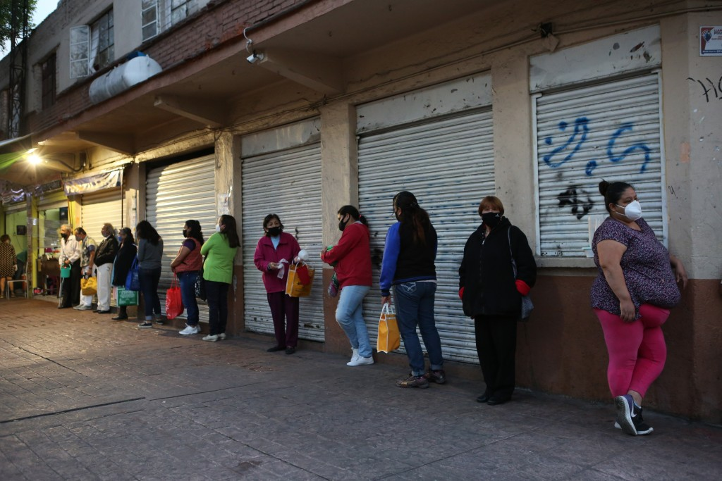 People line up for a free dinner at a soup kitchen in Mexico City, Saturday, Dec. 19, 2020, amid the COVID-19 pandemic. This soup kitchen is operated ...