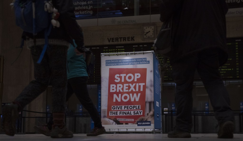 Passengers walk past a banner from the anti-Brexit campaign in Brussels, Sunday, Dec. 20, 2020. The EU and the United Kingdom were still working Sunda...