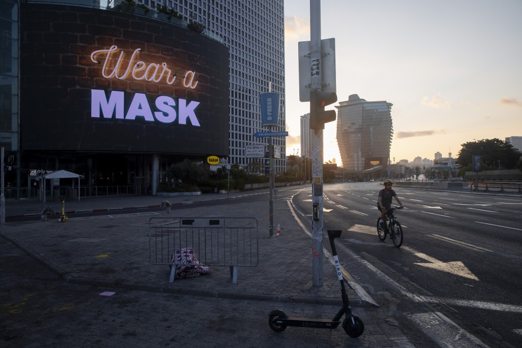 A man rides a bicycle next to a billboard calling people to wear masks, on empty road following new restrictions in the three-week nationwide lockdown...