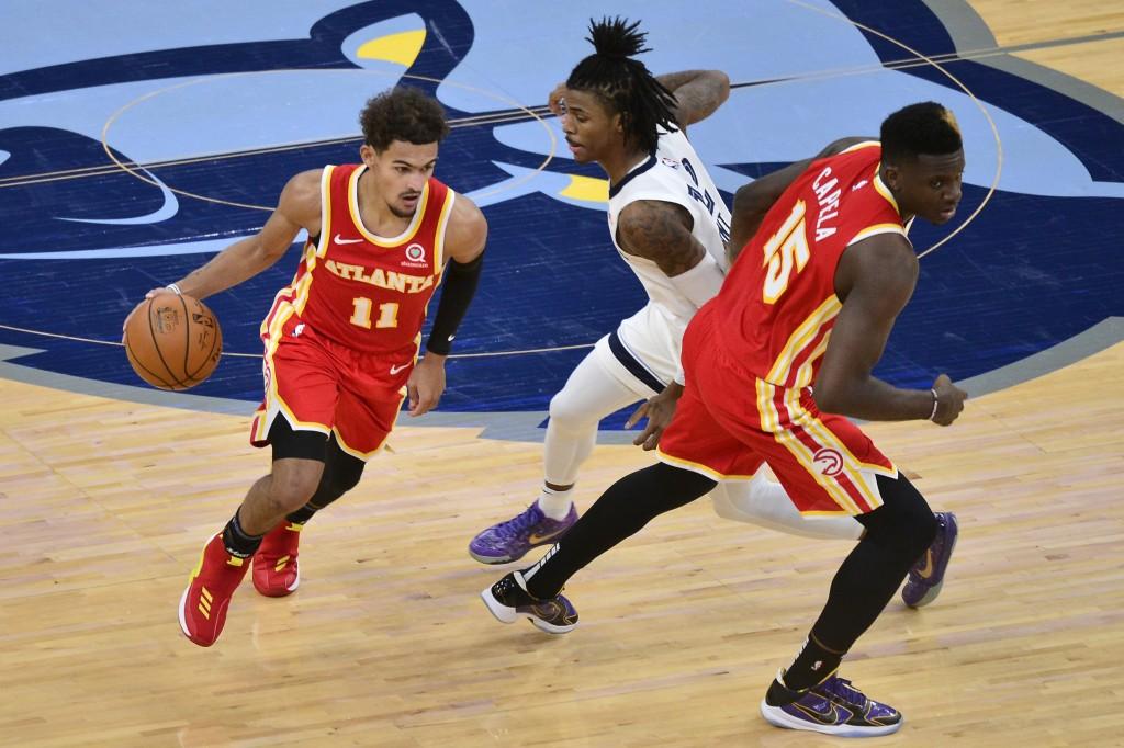 Atlanta Hawks guard Trae Young (11) drives past Memphis Grizzlies guard Ja Morant (12) as Hawks center Clint Capela (15) moves for position in the sec...