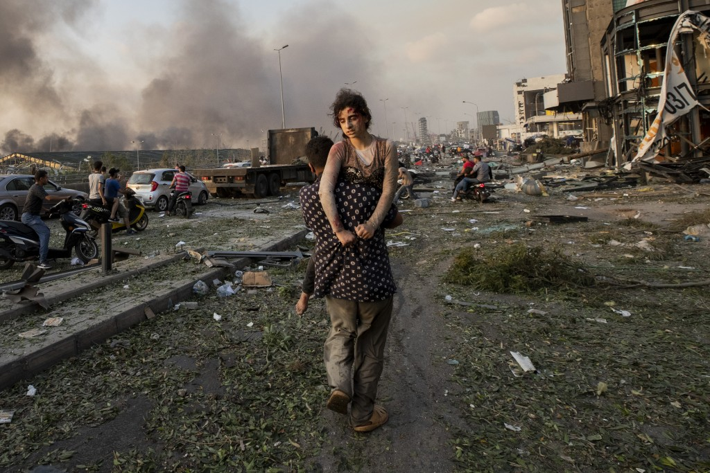 Hoda Kinno, 11, is evacuated by her uncle Mustafa, in the aftermath of a massive explosion at the port in Beirut, Lebanon, Aug. 4, 2020. The Kinno fam...