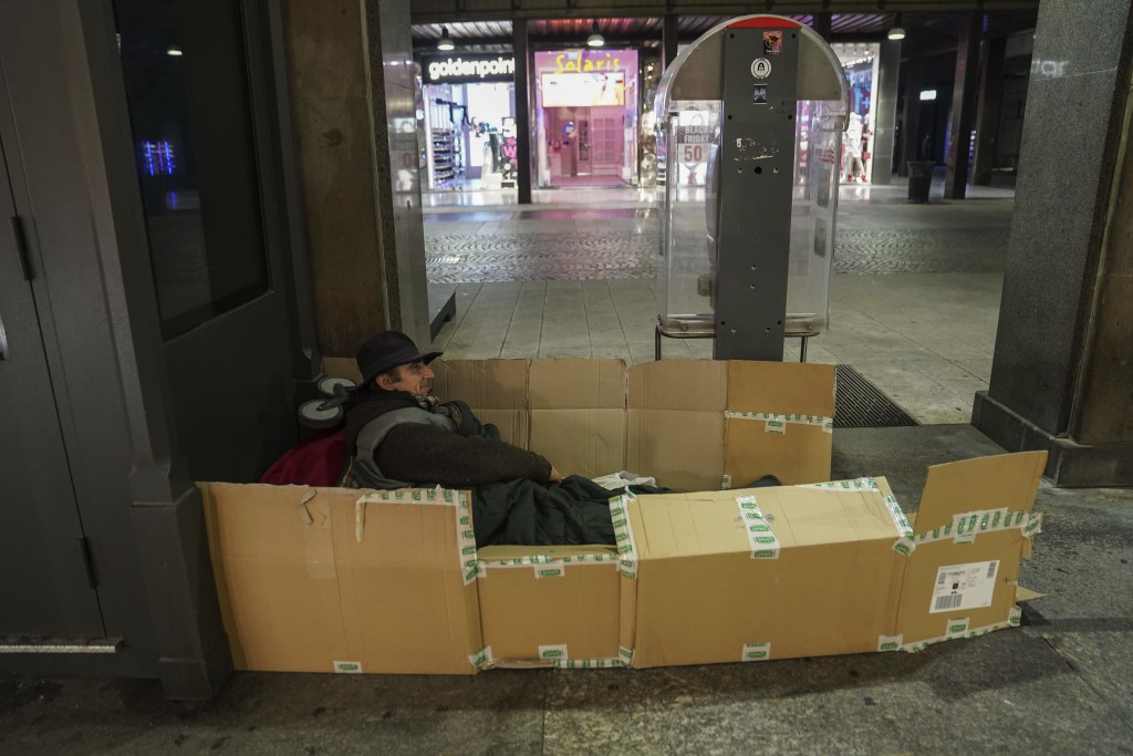 A homeless prepares himself for the night in downtown Milan, northern Italy, Friday, Nov. 27, 2020. Nowhere in Italy is poverty more evident than in L...