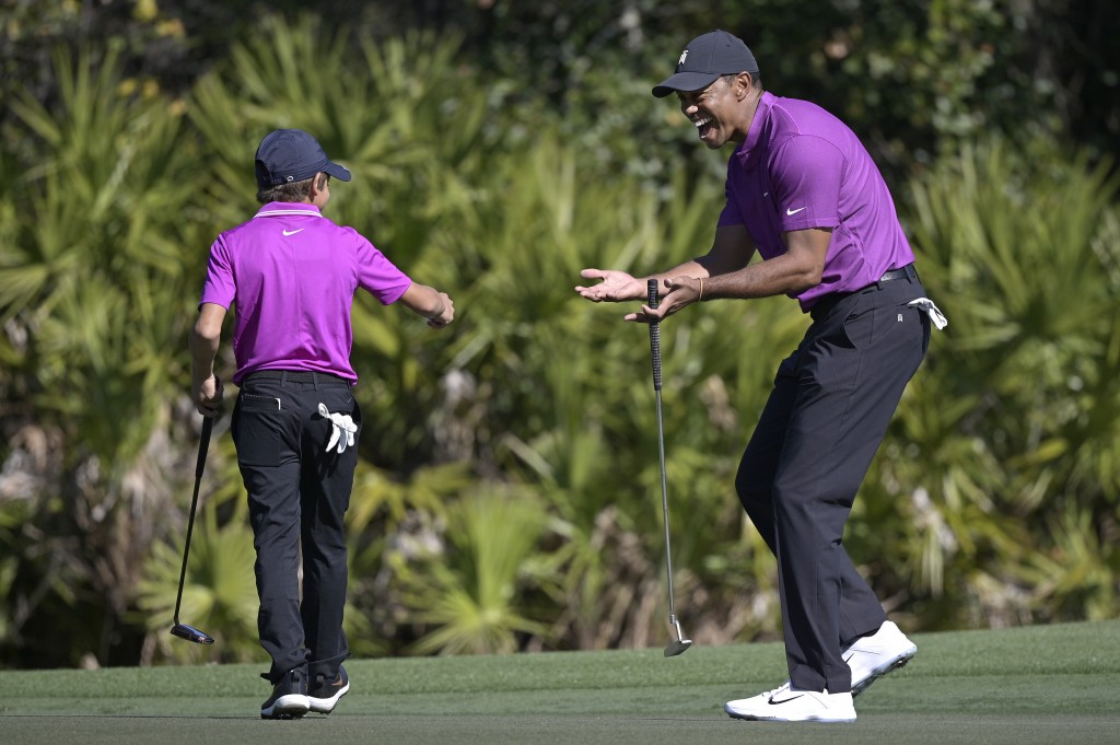 Tiger Woods, right, reacts after his son Charlie sank a putt on the third green during the first round of the PNC Championship golf tournament, Saturd...
