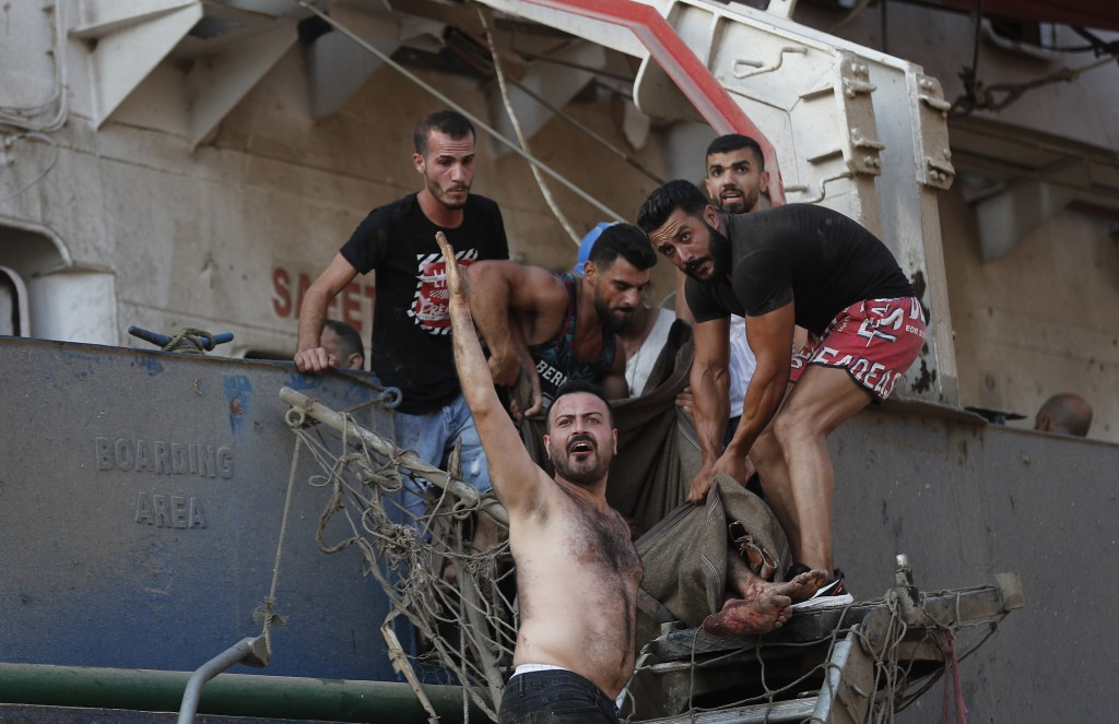 Civilians help to evacuate an injured sailor from a ship which dock near the explosion scene that hit the seaport of Beirut, Lebanon, Tuesday, Aug. 4,...