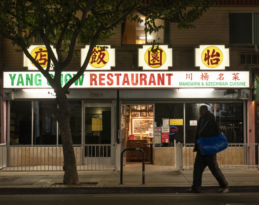 A man walks past the outside of Yang Chow restaurant at night in Los Angeles, Thursday, Dec. 17, 2020. Bigotry toward Asian Americans and Asian food h...