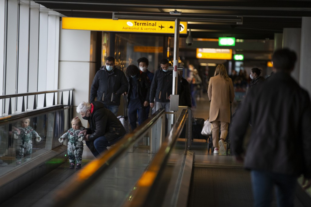 FILE- In this Friday Dec. 18, 2020, file photo, arriving and departing passengers use the flat escalators at Schiphol Airport, near Amsterdam, Netherl...