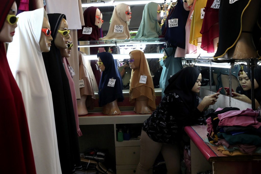 An employee uses her mobile phone as she waits for customers at a shop selling Muslim women's headscarves at a market in Jakarta, Indonesia, Wednesday...