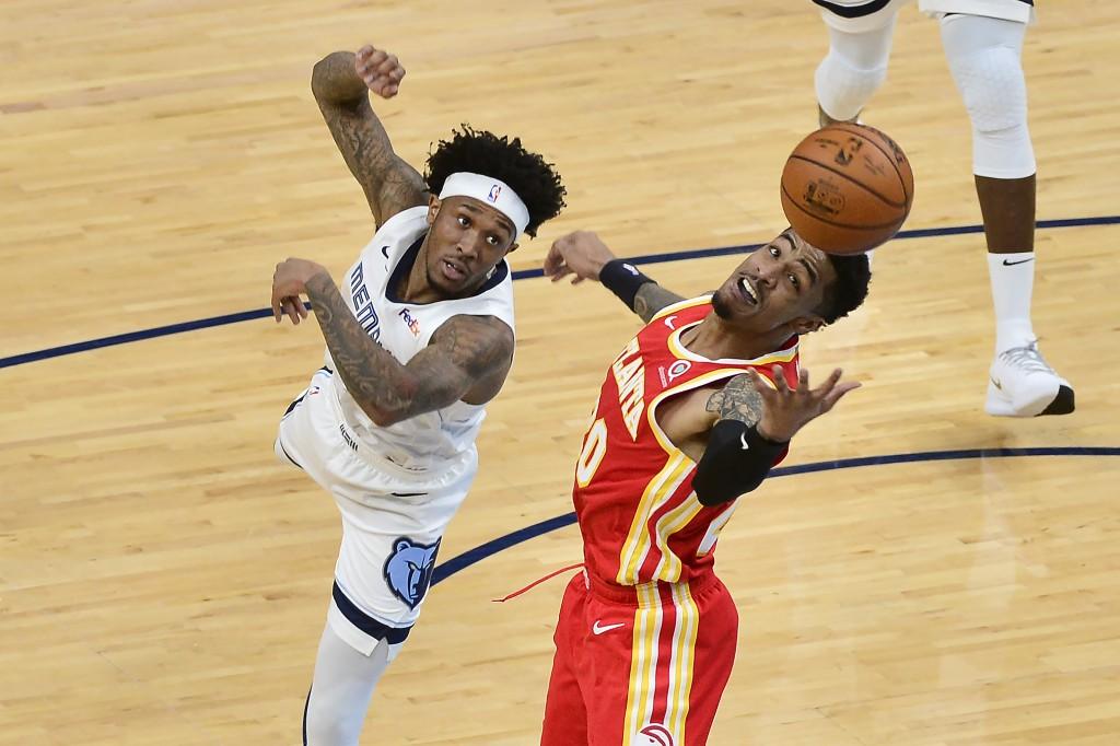 Memphis Grizzlies guard Ahmad Caver, left, and Atlanta Hawks forward John Collins (20) in the second half of an NBA preseason basketball game Saturday...
