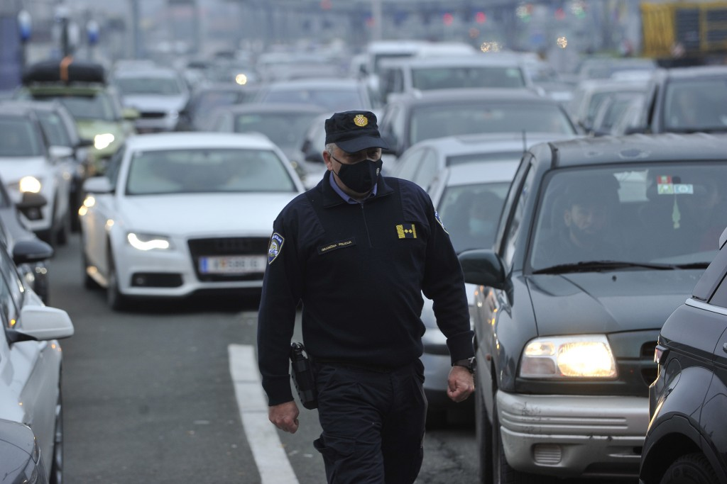 A Croatian border police officer walks between vehicles as motorists wait to cross the Croatian border from Slovenia, at Bregana border crossing, west...