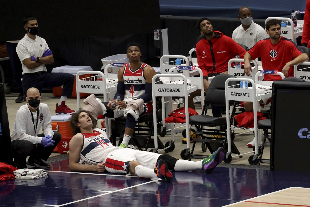 Washington Wizards Robin Lopez (15) and Russell Westbrook (4) watch from the bench during the first half of a preseason NBA basketball game against th...
