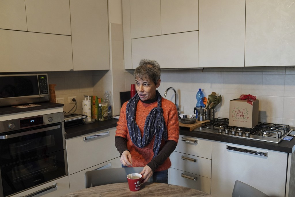 Elena Simone prepares an herbal tea in her kitchen during an interview with The Associated Press at her house in Novate Milanese, Italy, Friday, Dec. ...