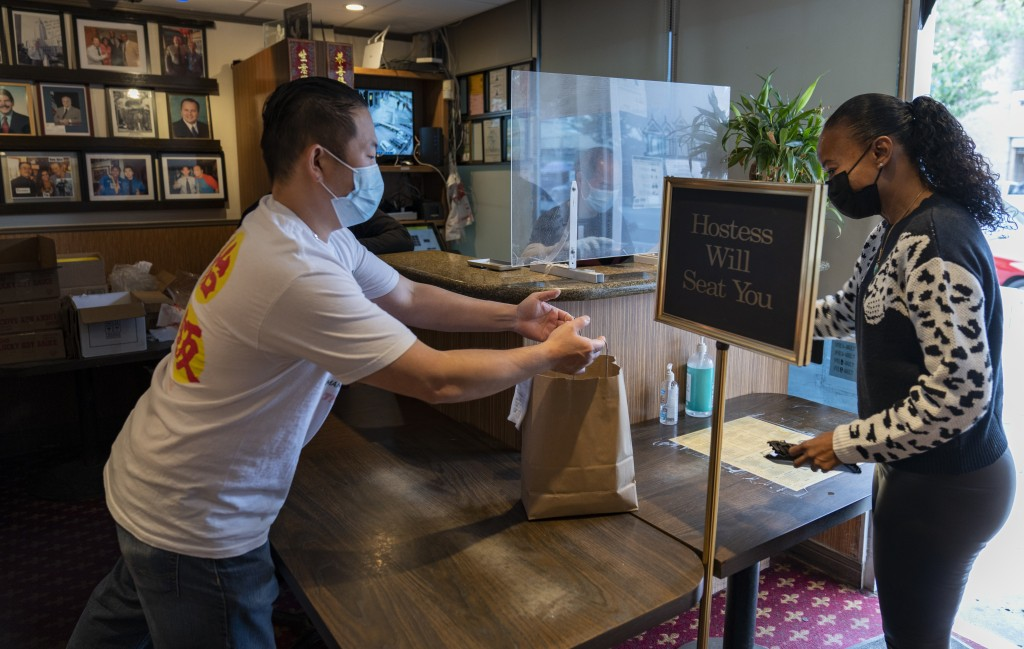 Benny Yun, owner of Yang Chow restaurant, left, delivers a take-out order in Los Angeles, Thursday, Dec. 17, 2020. Bigotry toward Asian Americans and ...