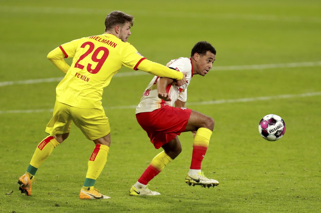 Cologne's Jan Thielmann, left, and Leipzig's Tyler Adams, right, challenge for the ball during the German Bundesliga soccer match between RB Leipzig a...