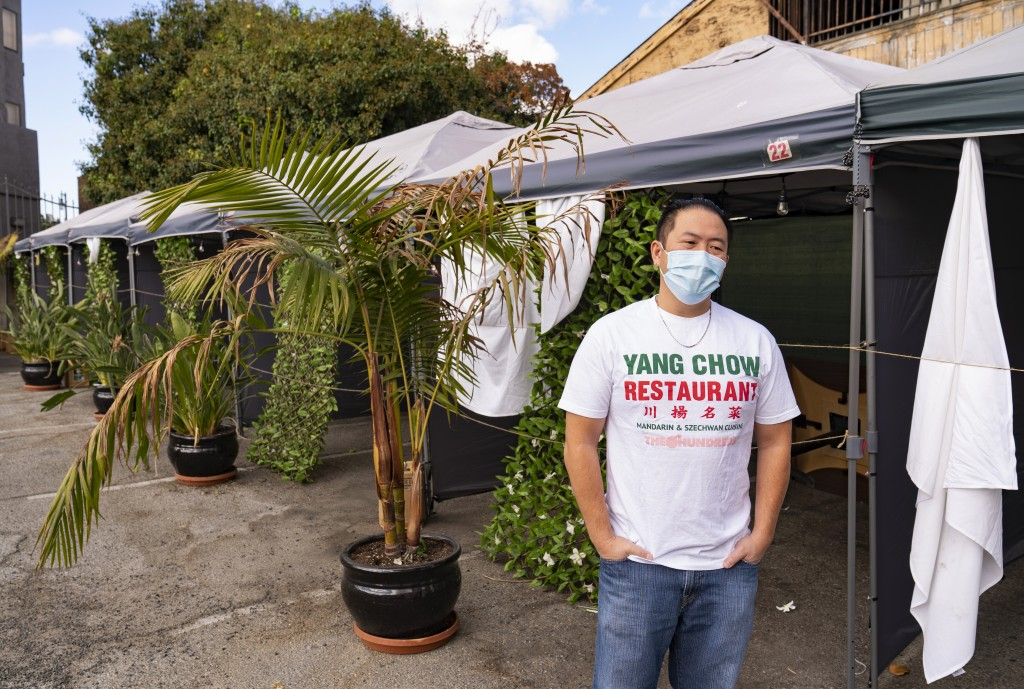 Benny Yun, owner of Yang Chow restaurant pauses next to now unused plastic tents set for clients to be able to eat outdoors on the parking lot of his ...