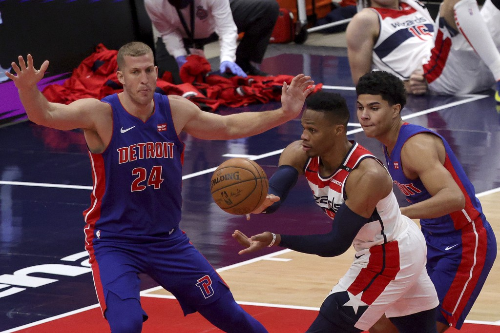 Washington Wizards Russell Westbrook (4) passes the ball between Detroit Pistons' Mason Plumlee (24) and Killian Hayes during the first half of a pres...