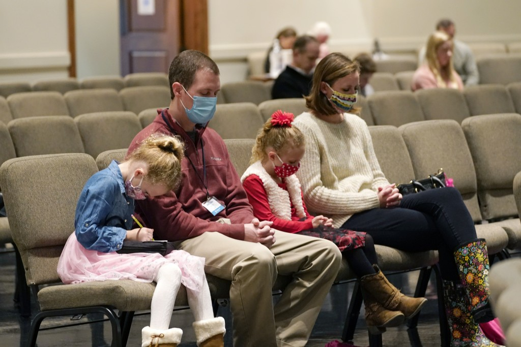 Jonathan Vaughn, second from left, and his family, Addison, 5, left, Ann Marie, 7, second from right, and wife Alesha Vaughn pray during services in t...