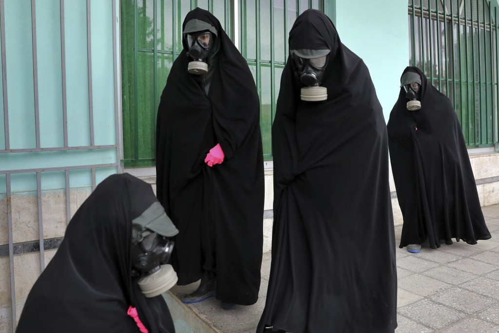 "Women clerics wearing protective clothing and ""chador,"" a head-to-toe garment, arrive at a cemetery to prepare the body of a person who died from COVI..."