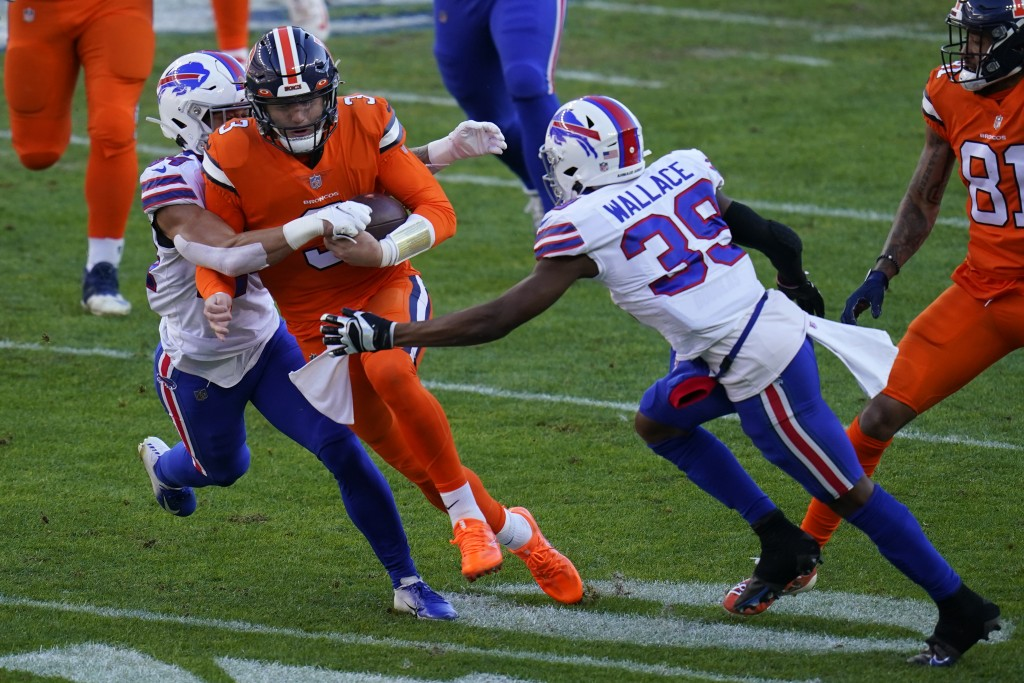 Denver Broncos quarterback Drew Lock, center, is brought down by Buffalo Bills cornerback Levi Wallace (39) and outside linebacker A.J. Klein during t...