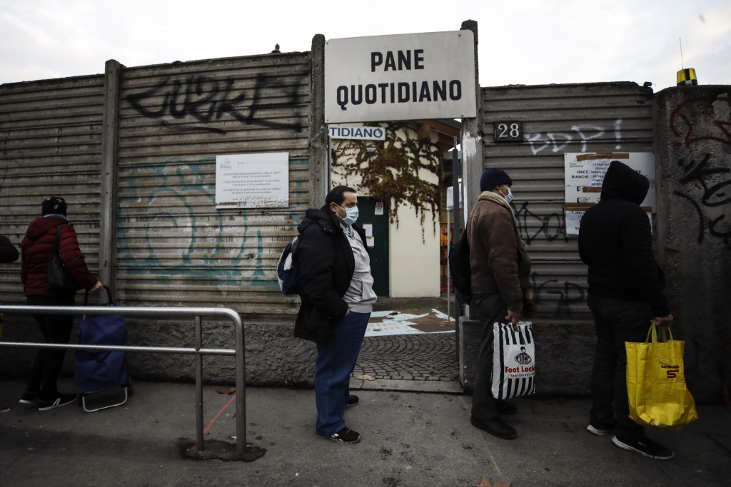 Maurizio Perrone, center, stands in the line for food at the 'Pane Quotidiano'(Daily Bread) Onlus, in Milan, northern Italy, Thursday, Dec. 17, 2020. ...