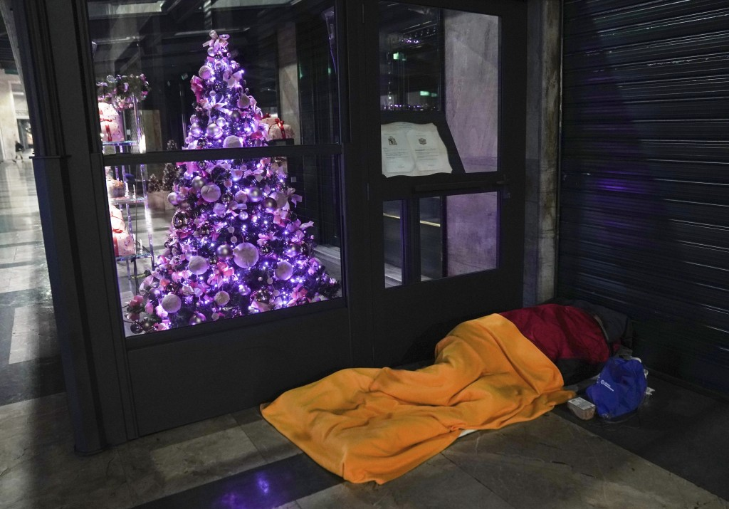 A homeless sleeps on the floor next to Christmas decoration outside a restaurant in downtown Milan, northern Italy, Friday, Nov. 27, 2020. Nowhere in ...