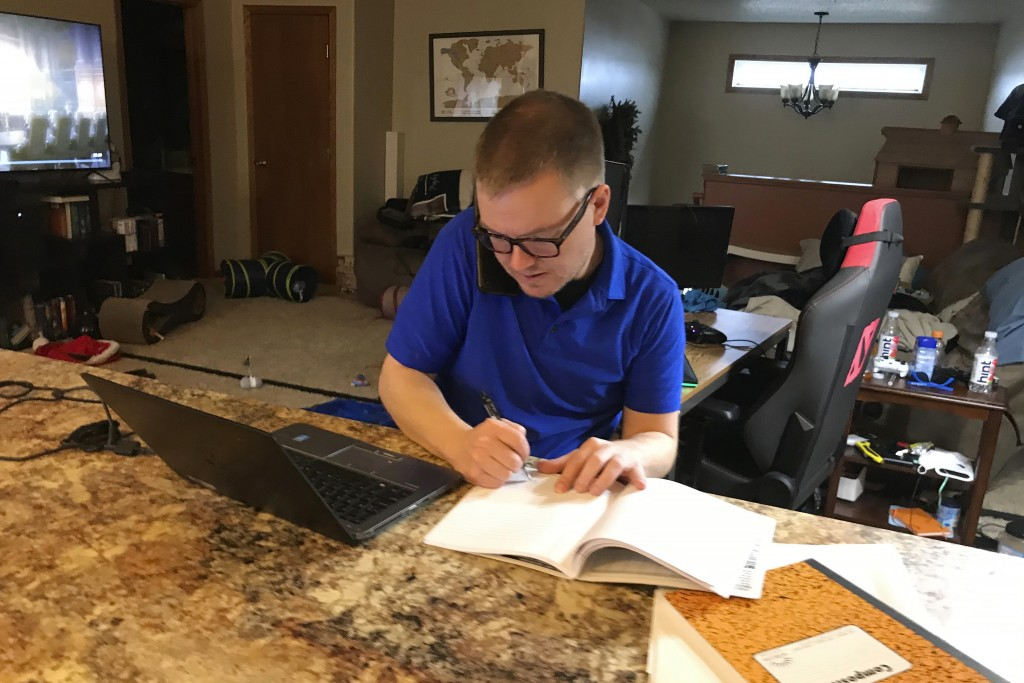 Brenton Nesemeier, who manages COVID-19 case managers and field managers at the North Dakota Department of Health, works at his home in Fargo, N.D., o...
