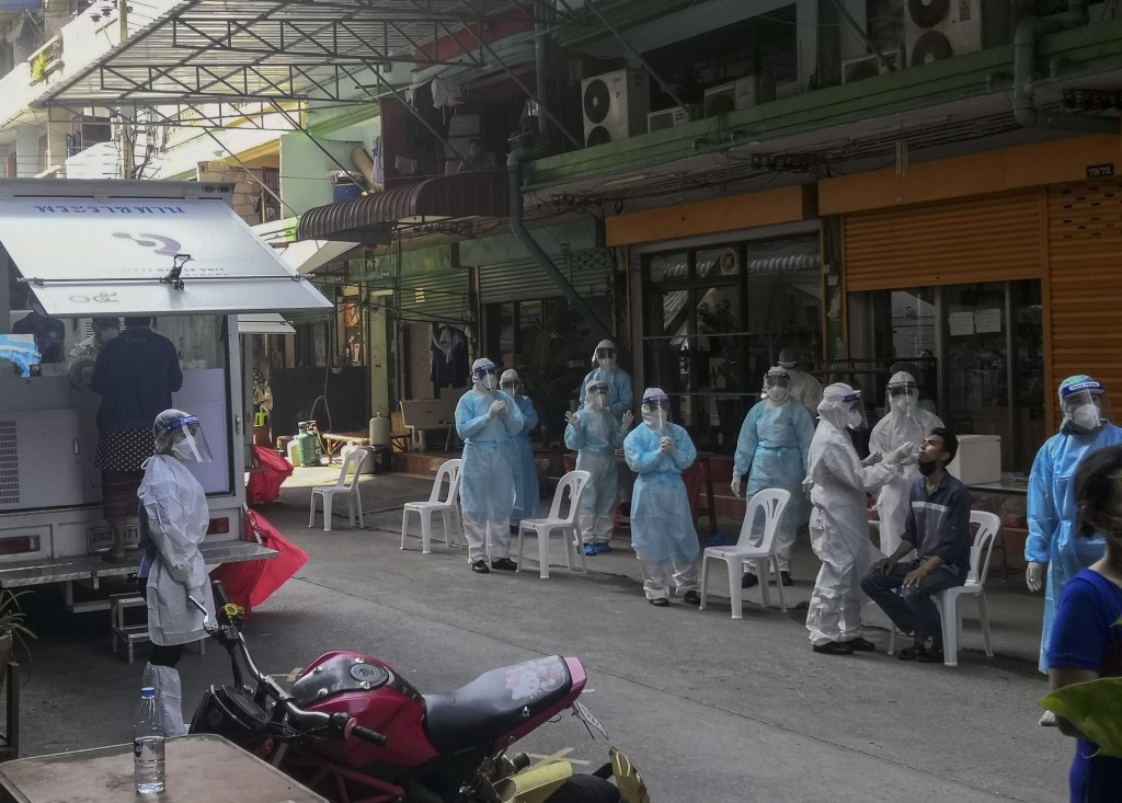 A health worker in protective clothing collects nasal swab sample from a man to test for COVID-19 in Samut Sakhon, South of Bangkok, Thailand, Sunday,...