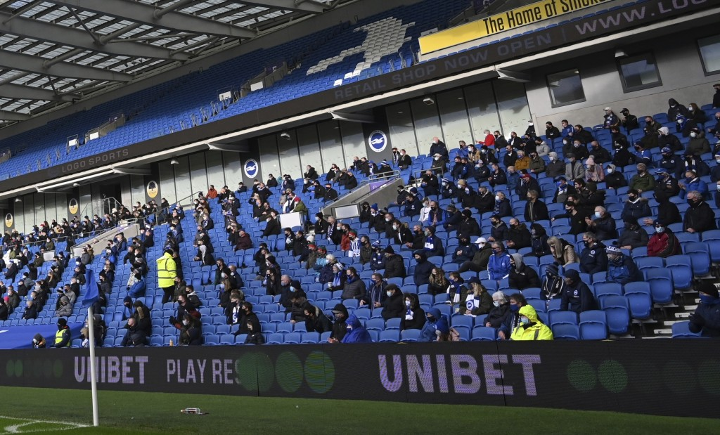 Fans, wearing a face mask, for covering due to the COVID-19 pandemic, sit socially distanced during the English Premier League soccer match between Br...