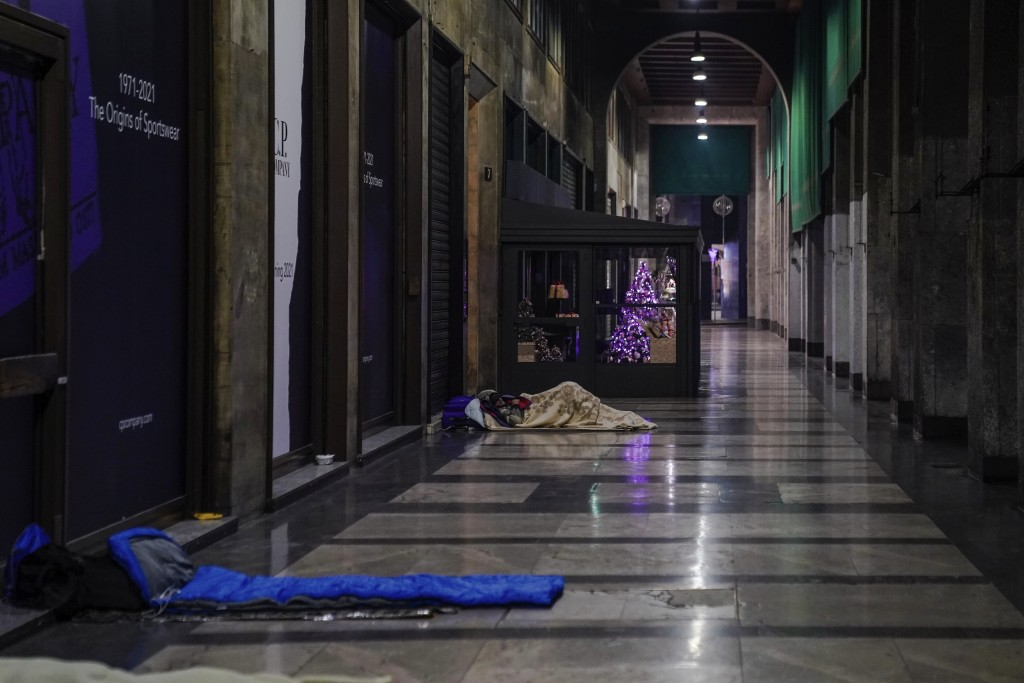 Homeless sleep on the floor of an arcade in downtown Milan, Italy, Friday, Nov. 27, 2020. Nowhere in Italy is poverty more evident than in Lombardy, t...