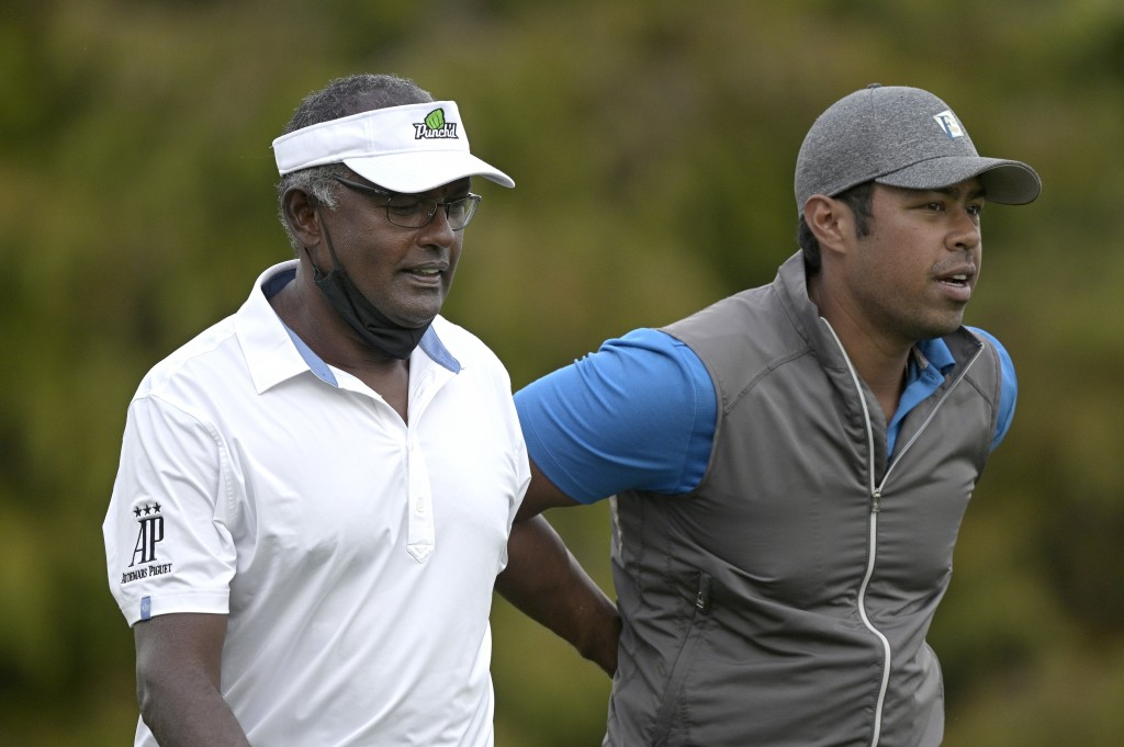 Vijay Singh, left, and his son Qass walk on the 18th fairway after hitting their tee shots during the first round of the PNC Championship golf tournam...