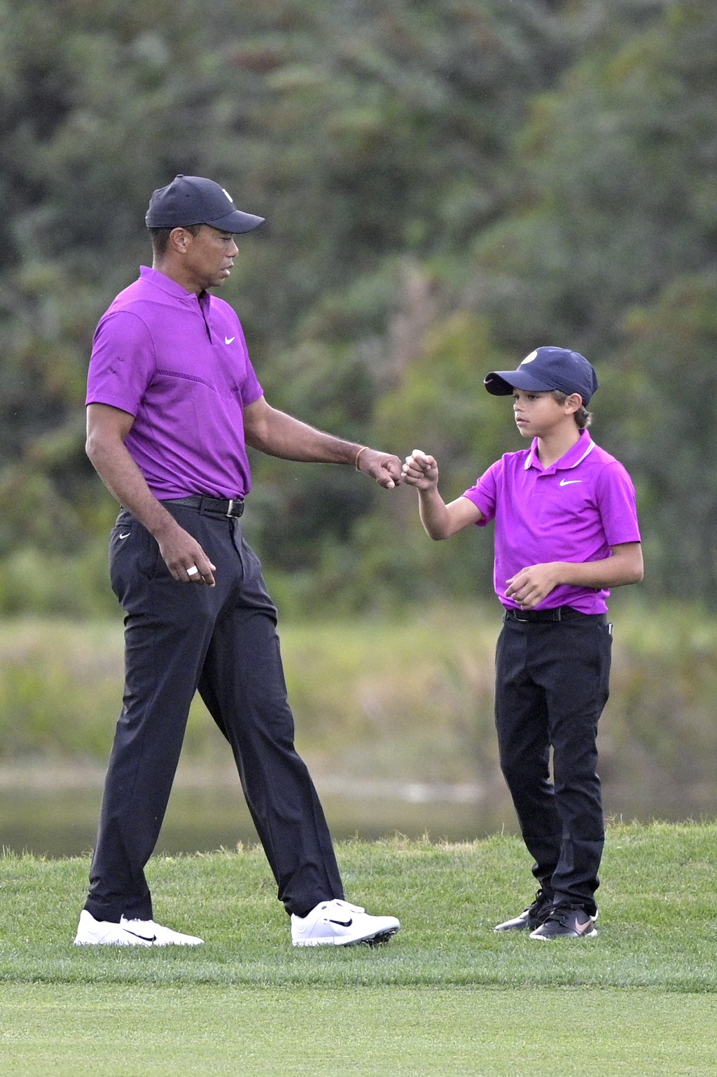 Tiger Woods, left, shares a fist-bump with his son Charlie after walking up their ball on the 14th fairway during the first round of the PNC Champions...
