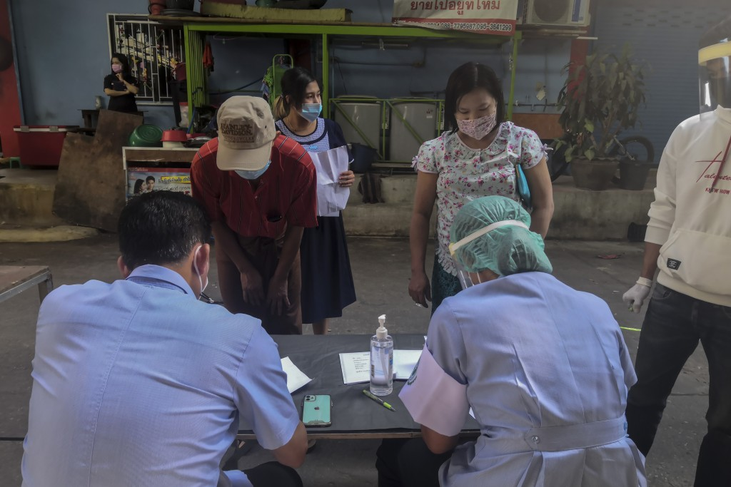 Health workers record migrant workers ahead of collecting nasal swab samples from them to test for COVID-19 in Samut Sakhon, south of Bangkok, Thailan...