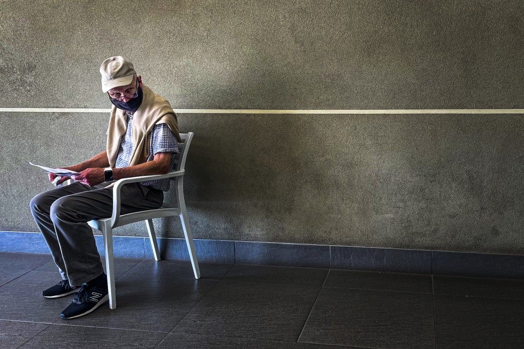 A lone man who was just tested for COVID-19 waits in line to make payment for the test at a private laboratory in Johannesburg, South Africa, Saturday...