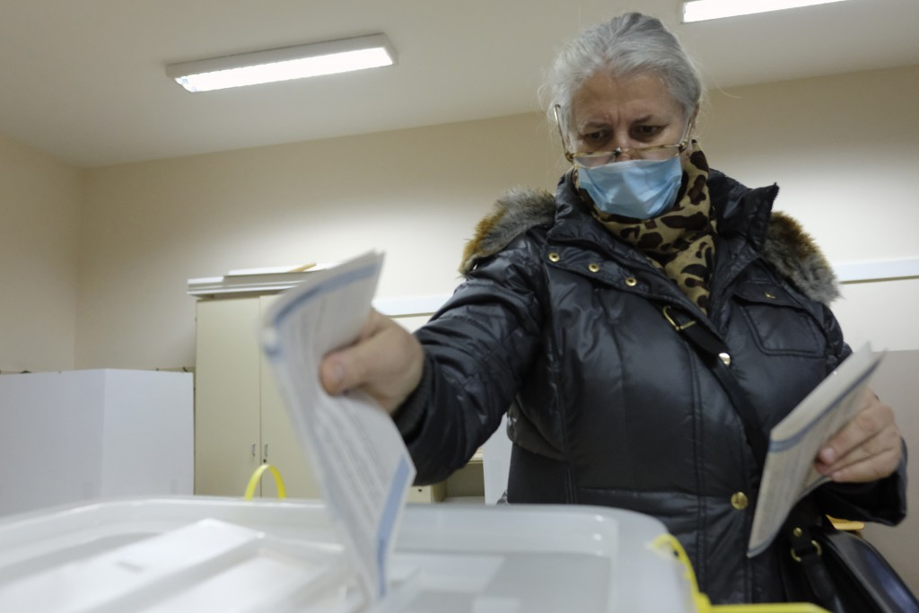 A woman casts her ballot for the local elections at a polling station in Mostar, Bosnia, Sunday, Dec. 20, 2020. Divided between Muslim Bosniaks and Ca...