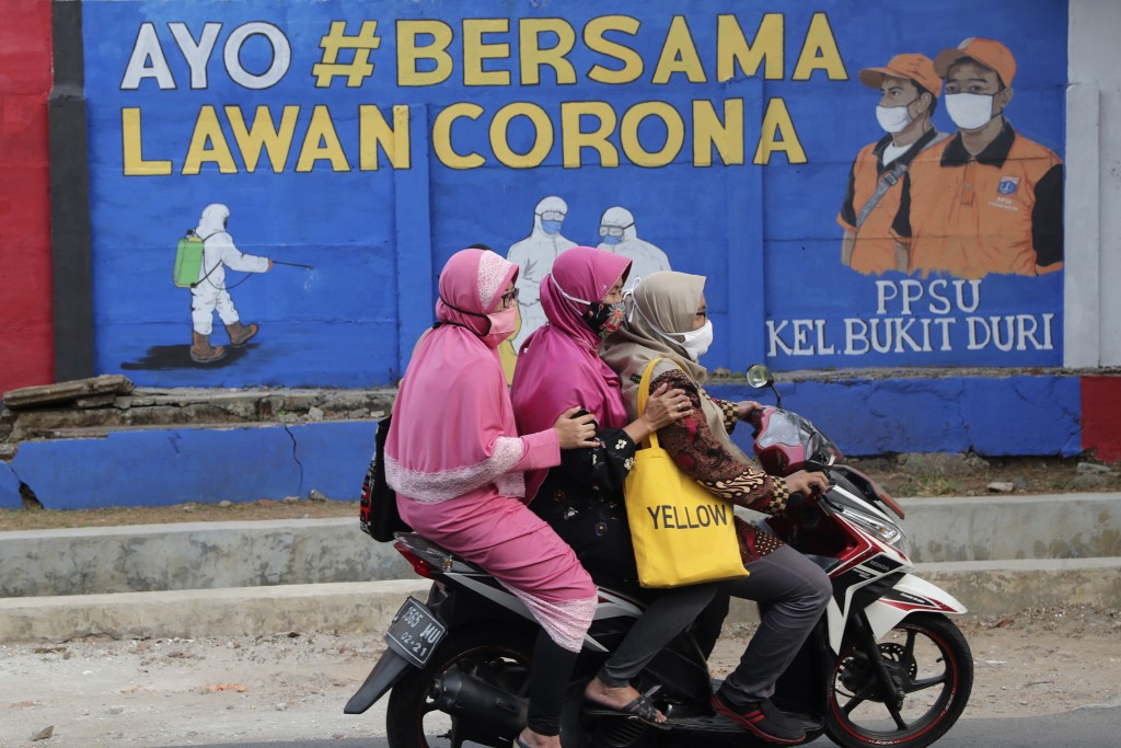 """Muslim women ride a motorbike past a coronavirus-themed mural in Jakarta, Indonesia, Thursday, Sept. 10, 2020. Writings on the mural read """"Let's fight..."""