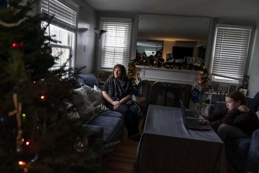 Eileen Carroll, left, sits for a portrait as her daughter, Lily, 11, attends school remotely from their home in Warwick, R.I, Wednesday, Dec. 16, 2020...