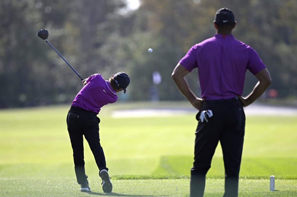 Tiger Woods, right, watches as his son Charlie tees off on the second hole during the first round of the PNC Championship golf tournament, Saturday, D...