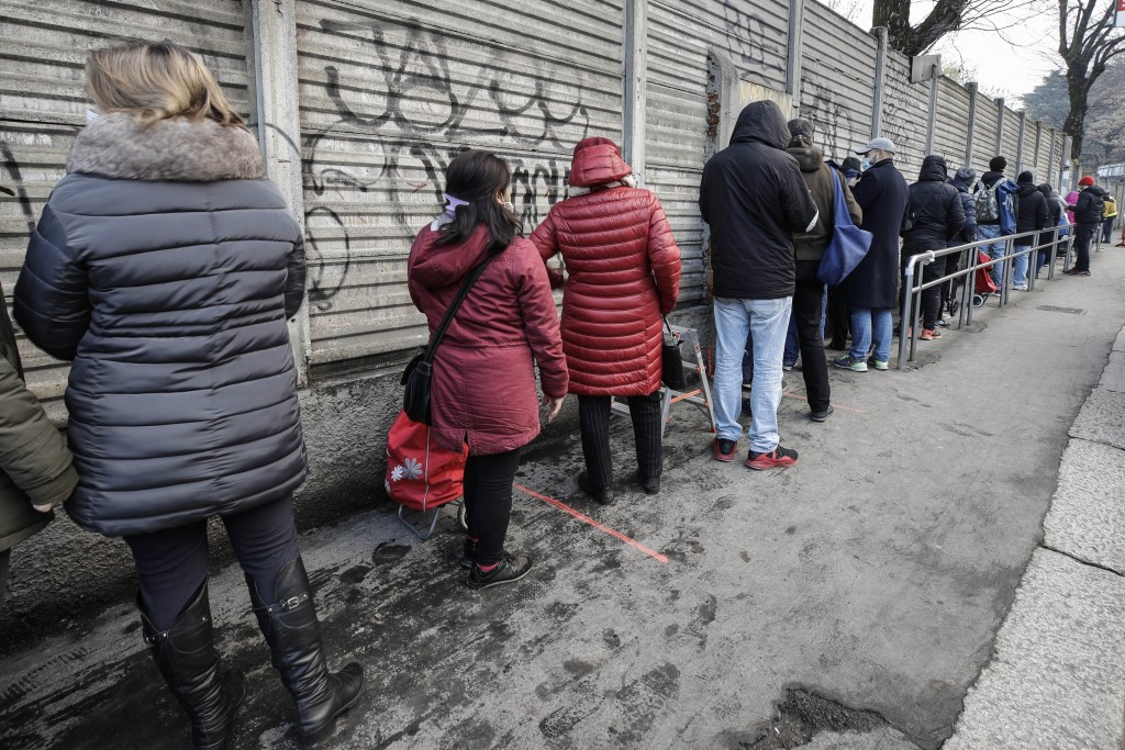 People queue for food at the 'Pane Quotidiano' (Daily Bread) Onlus, in Milan, northern Italy, Thursday, Dec. 17, 2020. Nowhere in Italy is poverty mor...